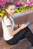 Mulher de negócio que guarda uma tabuleta em suas mãos com um sorriso em sua cara que senta-se no parque em um dia ensolarado per Fotos de Stock