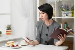 A mulher de negócio que lê o diário, vestido em um terno do cinza levanta na frente de uma parede branca foto de stock royalty free