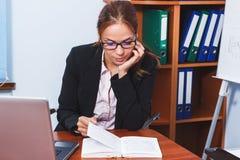 Mulher de negócio que lê um livro no escritório Imagem de Stock