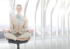Mulher de negócio que medita sobre a cadeira com o alargamento contra a janela branca obscura fotos de stock