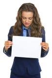 Mulher de negócio que mostra a folha do papel vazio Imagens de Stock