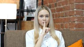 Mulher de negócio que mostra o gesto do silêncio, escritório interno fotografia de stock