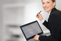 Mulher de negócio que mostra a tela e a pena do portátil Imagem de Stock Royalty Free