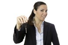 Mulher de negócio que oferece uma chave do carro Imagens de Stock