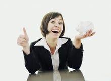 Mulher de negócio que põr o dinheiro das moedas no banco piggy Imagem de Stock Royalty Free