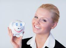 Mulher de negócio que prende um banco piggy Fotos de Stock