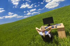 Mulher de negócio que relaxa na mesa no gabinete no terreno verde Fotografia de Stock