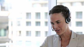 Mulher de negócio que ri ao falar em uns auriculares