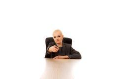 Mulher de negócio que senta-se atrás da mesa e que aponta na câmera Imagem de Stock Royalty Free