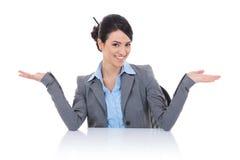 Mulher de negócio que senta-se atrás da mesa e que welcomming Fotografia de Stock Royalty Free