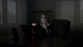 Mulher de negócio que senta-se em sua mesa que simula uma interação com um holograma com a tela aumentada da realidade em seu por vídeos de arquivo