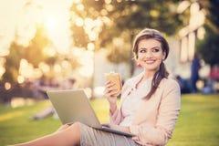 Mulher de negócio que senta-se em um parque Imagem de Stock