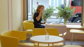 Mulher de negócio que senta-se em uma tabela em um café bebendo do café e que trabalha em um portátil filme