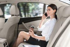 Mulher de negócio que senta-se no carro e que fala no telefone fotos de stock royalty free