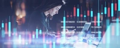 Mulher de negócio que senta-se no escritório da noite no laptop dianteiro e que usa seu telefone celular Castiçal vermelho e verd imagens de stock