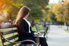 Mulher de negócio que senta-se no parque em um banco, trabalhando com um portátil imagens de stock royalty free
