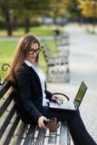 Mulher de negócio que senta-se no parque em um banco, trabalhando com um portátil fotos de stock royalty free