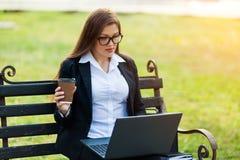 Mulher de negócio que senta-se no parque em um banco, trabalhando com um portátil fotos de stock