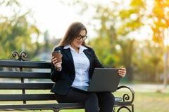 Mulher de negócio que senta-se no parque em um banco, trabalhando com um portátil imagens de stock