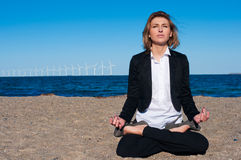 A mulher de negócio que senta-se nos lótus levanta na praia, Fotos de Stock