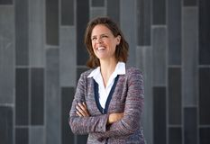 A mulher de negócio que sorri com braços cruzou-se contra o fundo cinzento Foto de Stock