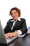 Mulher de negócio que trabalha alegre em sua mesa Imagem de Stock Royalty Free