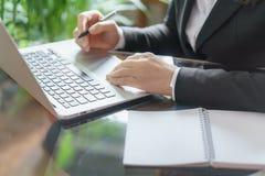 Mulher de negócio que trabalha com portátil, caderno e pena imagem de stock