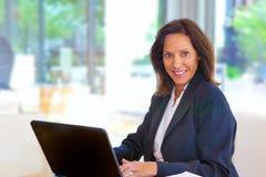 Mulher de negócio que trabalha em seu portátil Fotografia de Stock Royalty Free