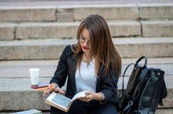 Mulher de negócio que trabalha na rua Senta-se nas etapas com um café e um bloco de notas do portátil Fotos de Stock