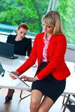 Mulher de negócio que trabalha na tabuleta com o colega no fundo Imagem de Stock Royalty Free