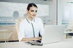Mulher de negócio que trabalha no portátil fotografia de stock