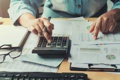 mulher de negócio que usa a calculadora para calcular do original dos dados Imagem de Stock