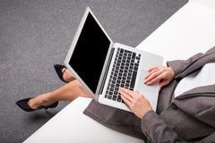 Mulher de negócio que usa o portátil ao sentar-se no sofá Foto de Stock Royalty Free