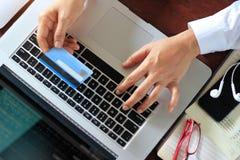 Mulher de negócio que usa o portátil com cartão de crédito à disposição fotografia de stock