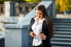 Mulher de negócio que usa o telefone ao andar exterior fotos de stock