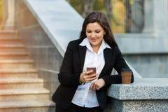 Mulher de negócio que usa o telefone ao andar exterior imagens de stock royalty free