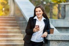Mulher de negócio que usa o telefone ao andar exterior imagens de stock