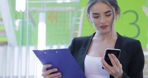 Mulher de negócio que usa o telefone celular em escadas no centro do escritório filme