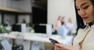A mulher de negócio que usa o telefone esperto da pilha no escritório sobre a equipe criativa dos empresários discute o projeto n vídeos de arquivo