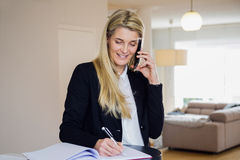 Mulher de negócio que usa seu telefone e fazendo anotações Fotografia de Stock