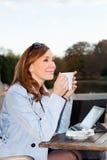 Mulher de negócio que usa a tabuleta na pausa para o almoço. Imagem de Stock