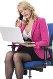 Mulher de negócio que usa um laptop e um telefone celular móvel Foto de Stock Royalty Free