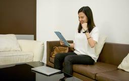Mulher de negócio que usa uma tabuleta na sala de visitas na noite imagem de stock