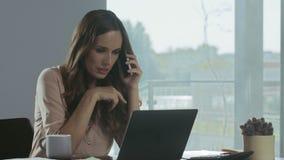 Mulher de negócio que verifica o portátil em casa Pessoa feliz que conversa no telefone celular filme