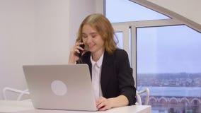 Mulher de negócio séria que fala pelo laptop dianteiro do telefone celular no escritório filme