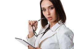 Mulher de negócio 'sexy' com vidros com a tabuleta em um fundo branco Fotografia de Stock Royalty Free