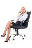 Mulher de negócio 'sexy' que senta-se na cadeira do escritório isolada no branco Foto de Stock