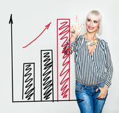 Mulher de negócio de sorriso com cartas de aumentação vermelhas da seta e dos gráficos Fotografia de Stock Royalty Free