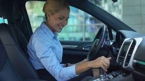 Mulher de negócio de sorriso deleitada com a compra do carro, tocando no salão de beleza do automóvel video estoque