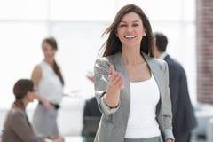 Mulher de negócio de sorriso que guarda para fora sua mão para um aperto de mão foto de stock